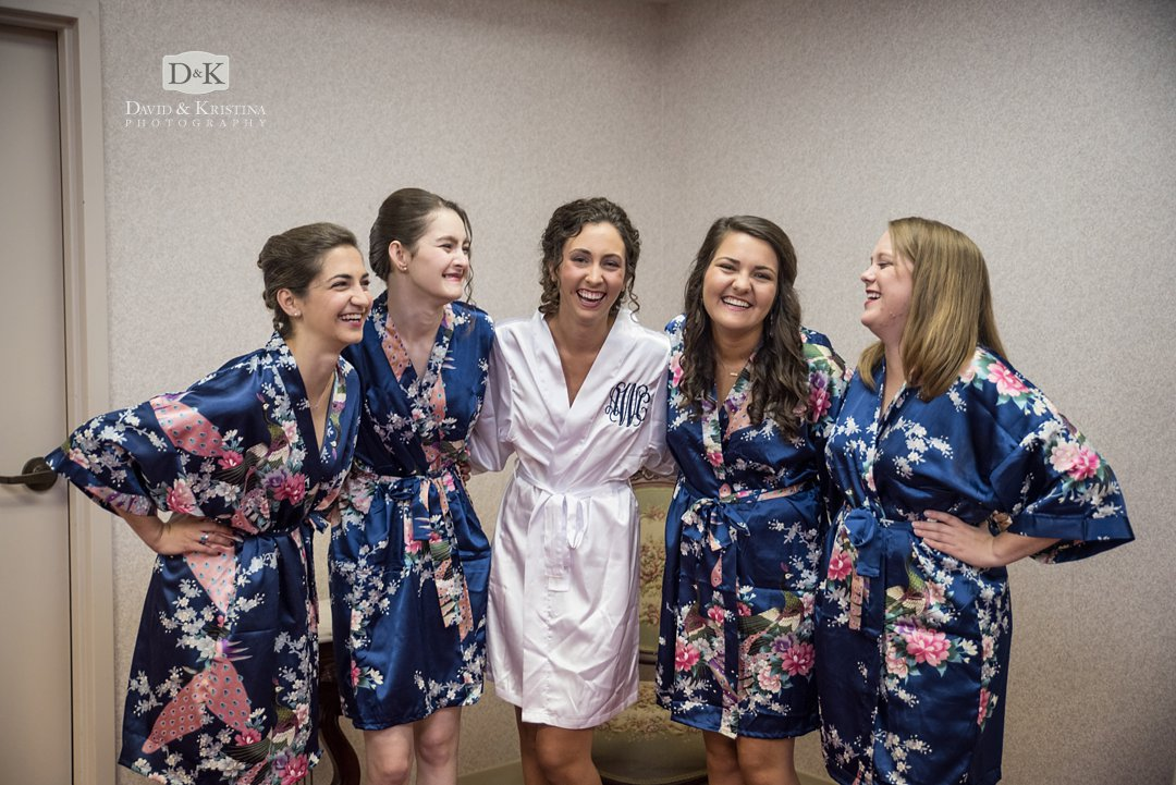 bride in white robe bridesmaids in navy floral robes
