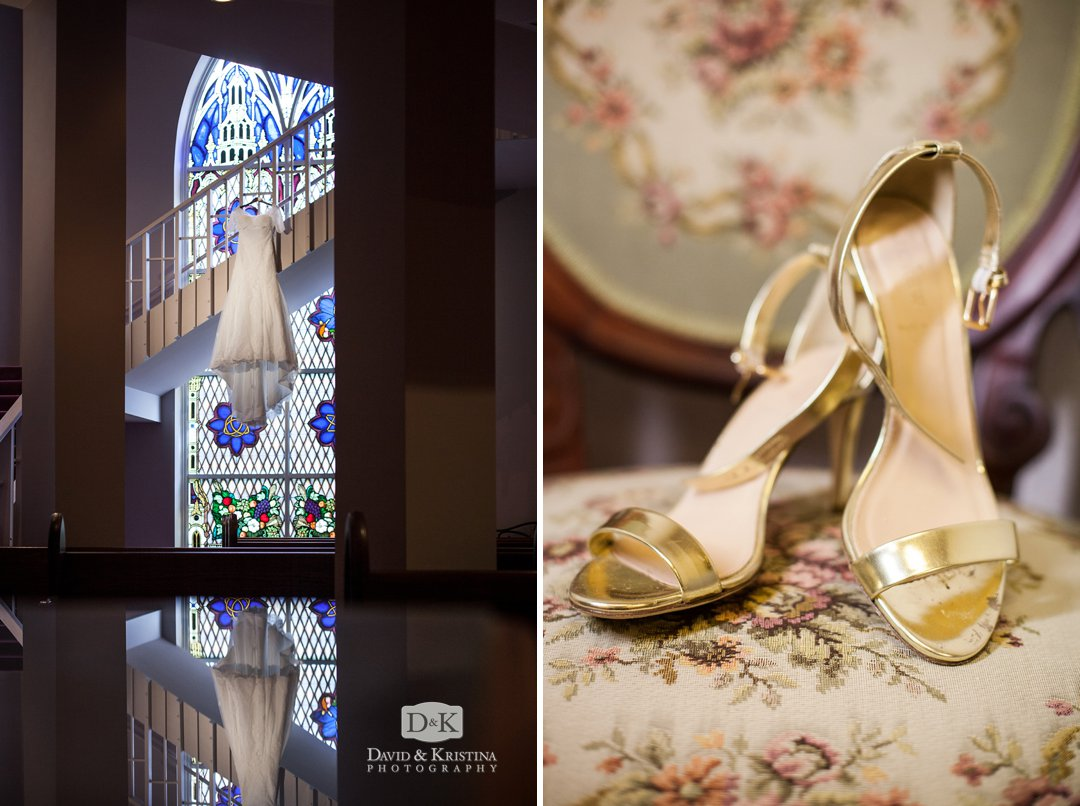 wedding dress hanging in front of stained glass window and bride's gold wedding shoes
