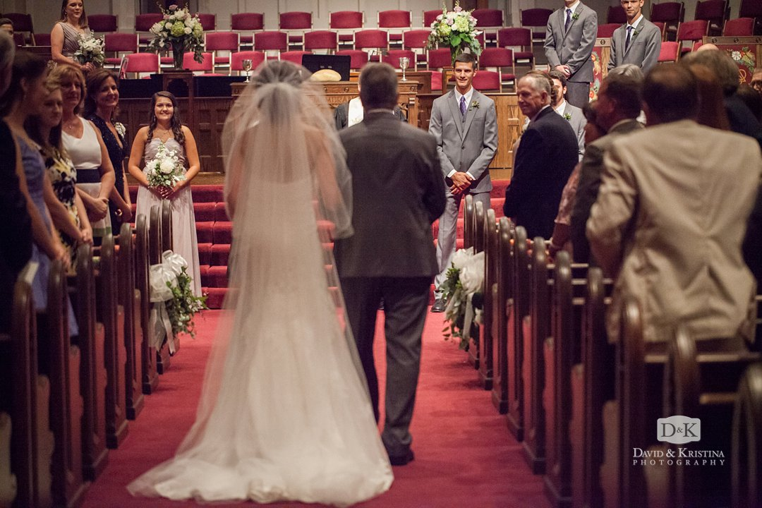 Aubrey walking with her father down the aisle toward Craig