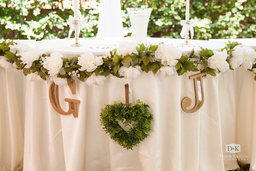 Gold initials hanging on sweetheart table