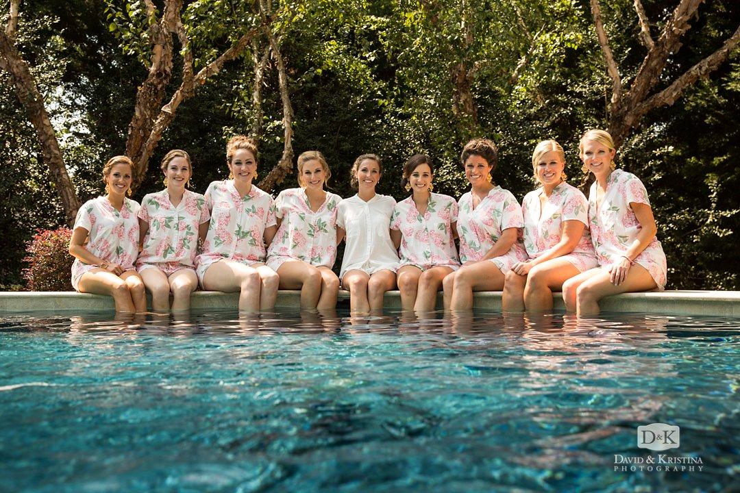 bridesmaids sitting on edge of pool in pajamas