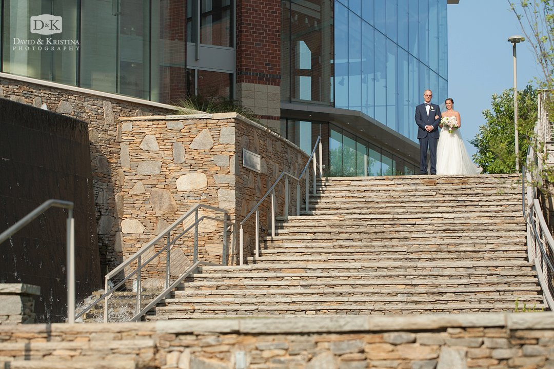 bride walking down steps behind Peace Center