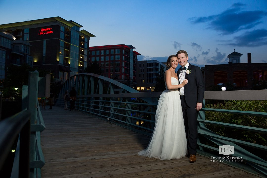 bride and groom at dusk on green bridge over Reedy River