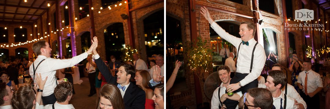 groom carried up in the air on a chair during hora dance