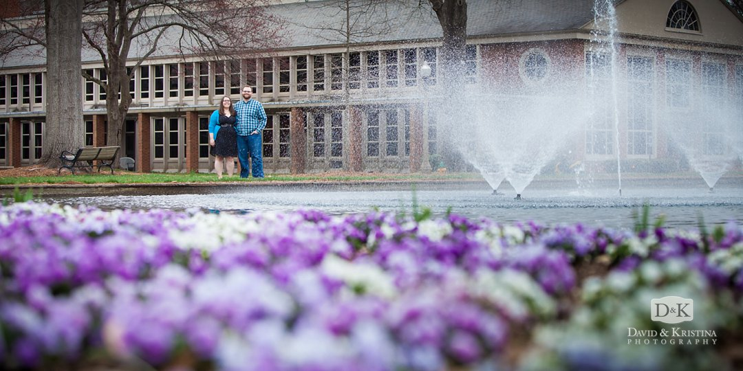 engagement picture with purple flowers in front of Furman Library