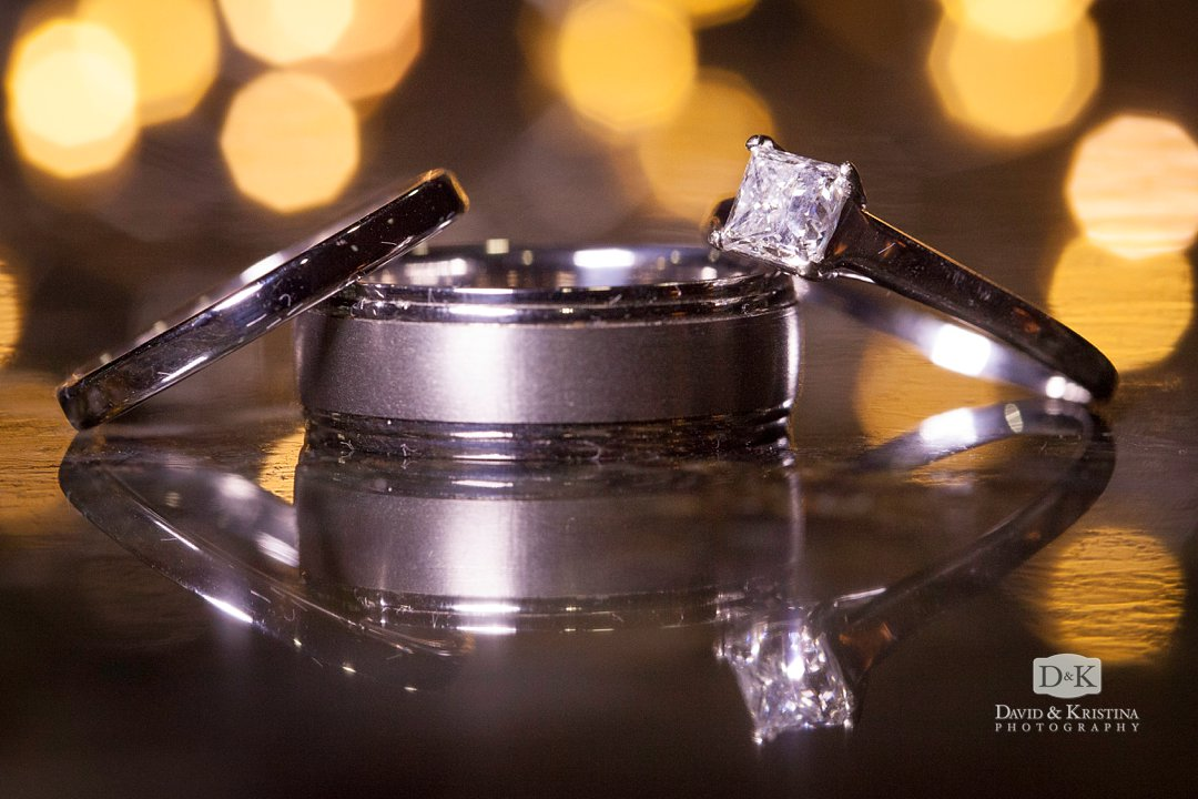 close up of wedding rings with twinkle lights in background