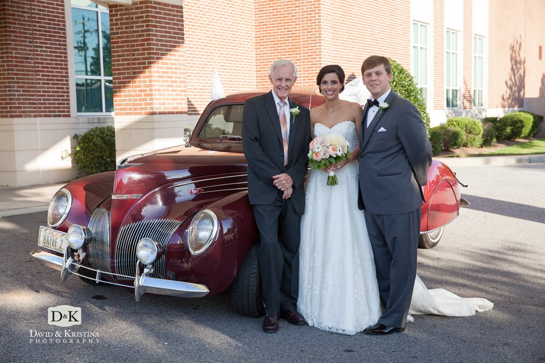 Bride and groom with grandfather's old car for wedding getaway car