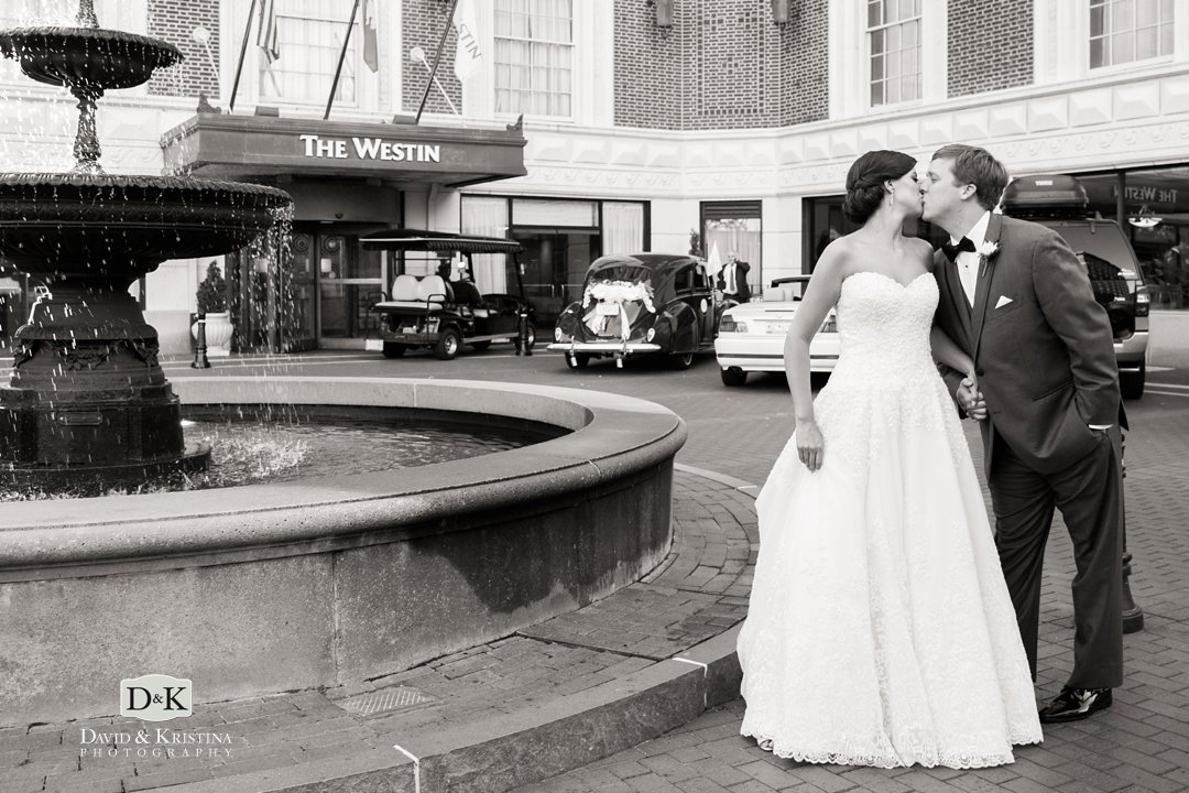 bride and groom kissing in front of Westin Poinsett