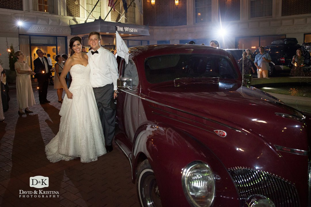 Bride and groom with old classic getaway car 1939 Lincoln Zephyr