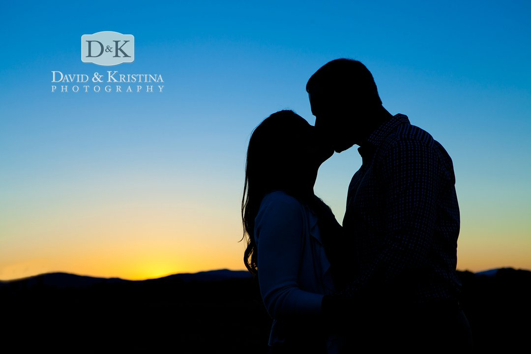 silhouette kissing engagement photo at sunset