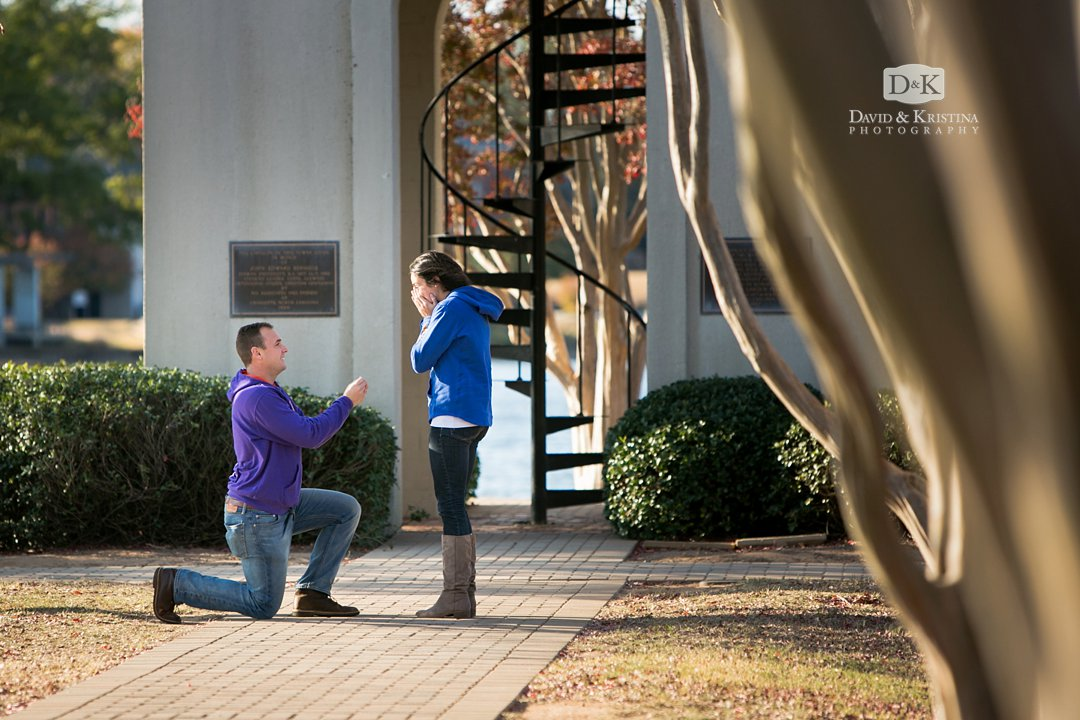 guy on one knee proposal at Furman Belltower by the lake
