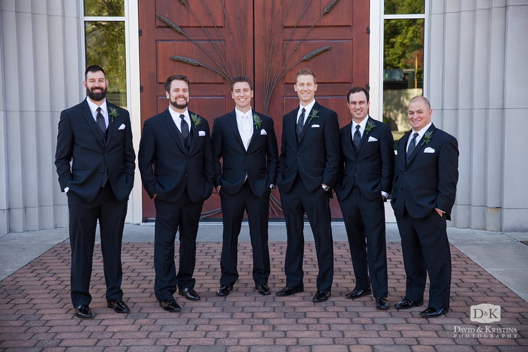groomsmen in front of wooden doors of Prince of Peace