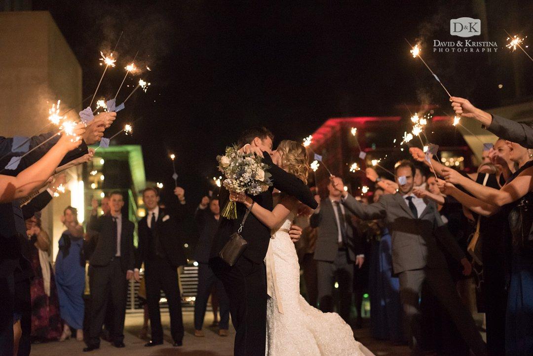 bride and groom kissing during sparkler exit