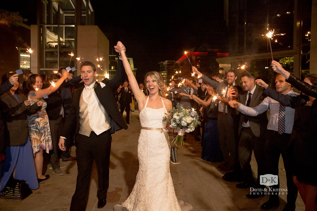 bride and groom with arms in the air at sparkler exit