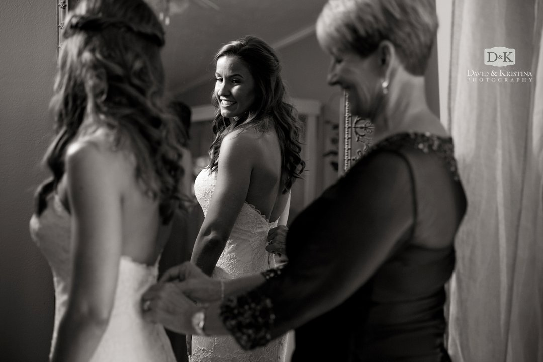 bride's mother helping put on dress
