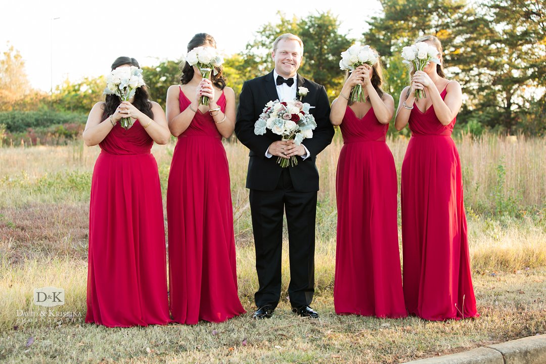 groom holding bouquet with bridesmaids in red dresses