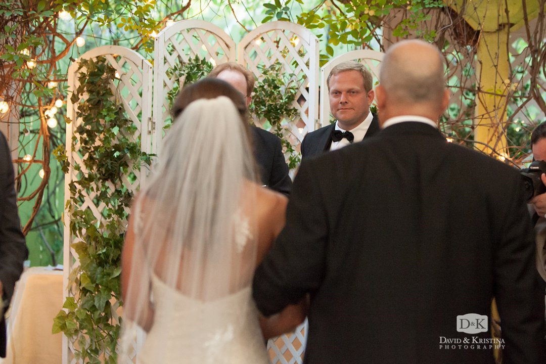 Groom's face watching bride walk toward him