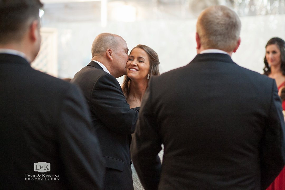 dad kisses daughter as he gives her away
