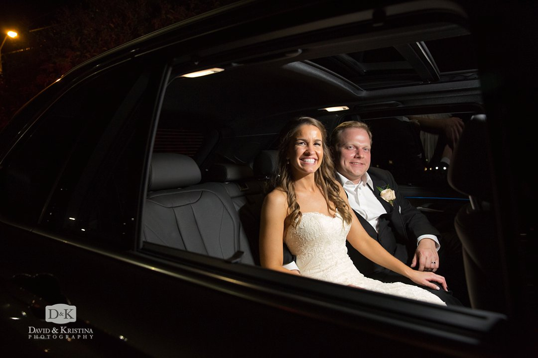 bride and groom leaving in black BMW