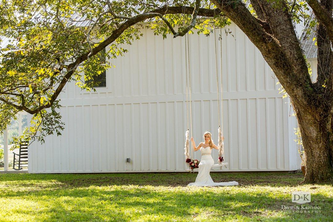 bride on rope swing under big oak tree
