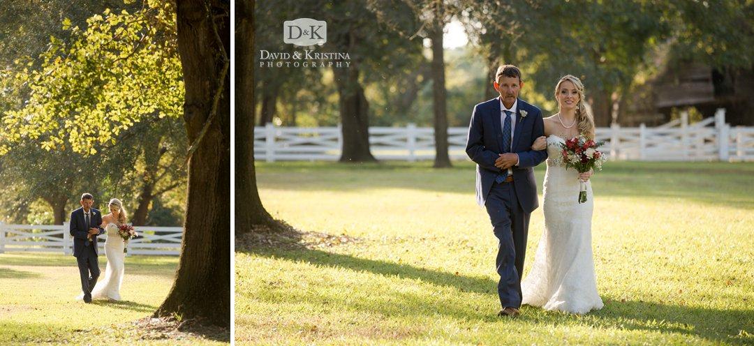 bride walking through oak trees toward wedding