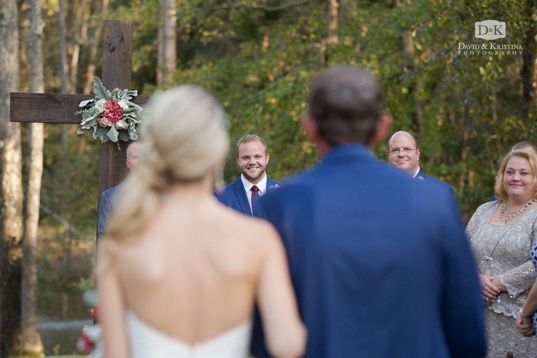 groom watching bride walk toward him