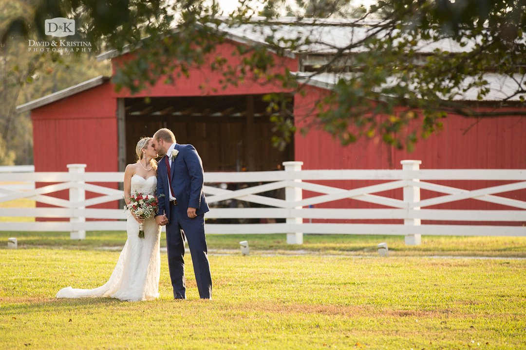 Bride and groom in front of red barn at Wildberry Farm