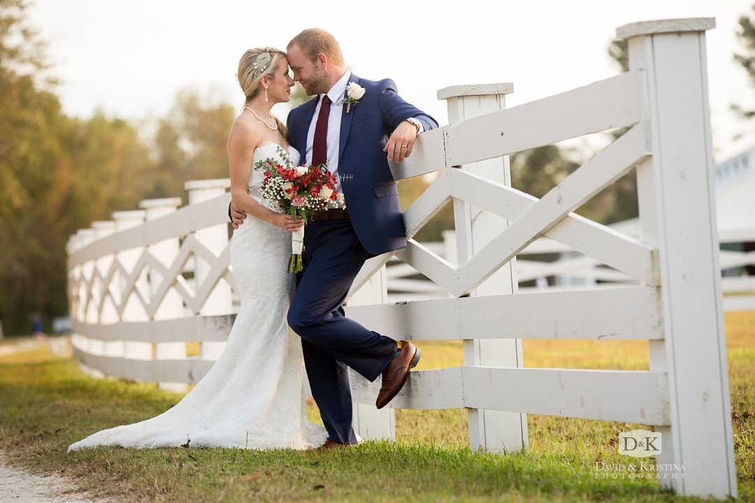 white fence with bride and groom