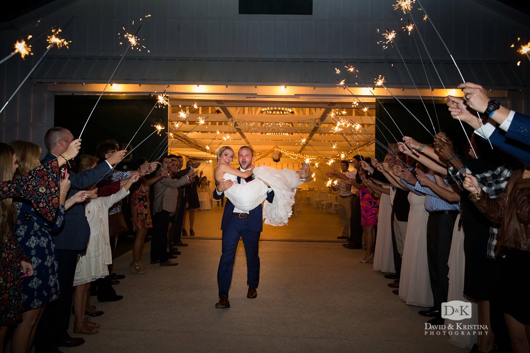 Groom carries bride through sparkler exit