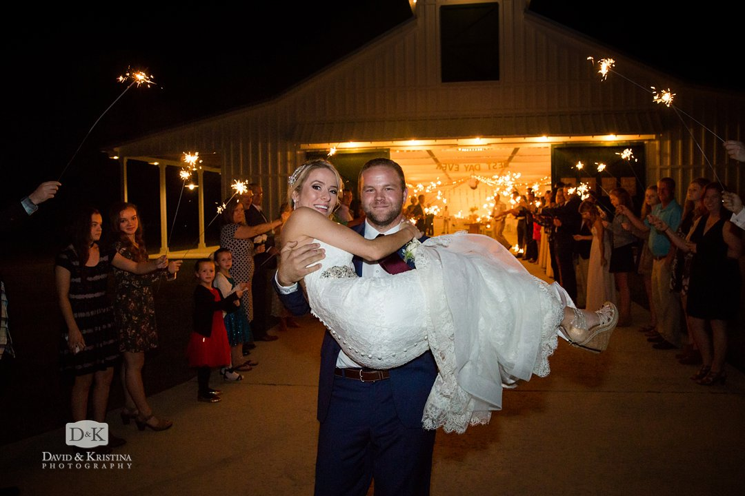 Groom carrying bride through sparklers at the end of wedding