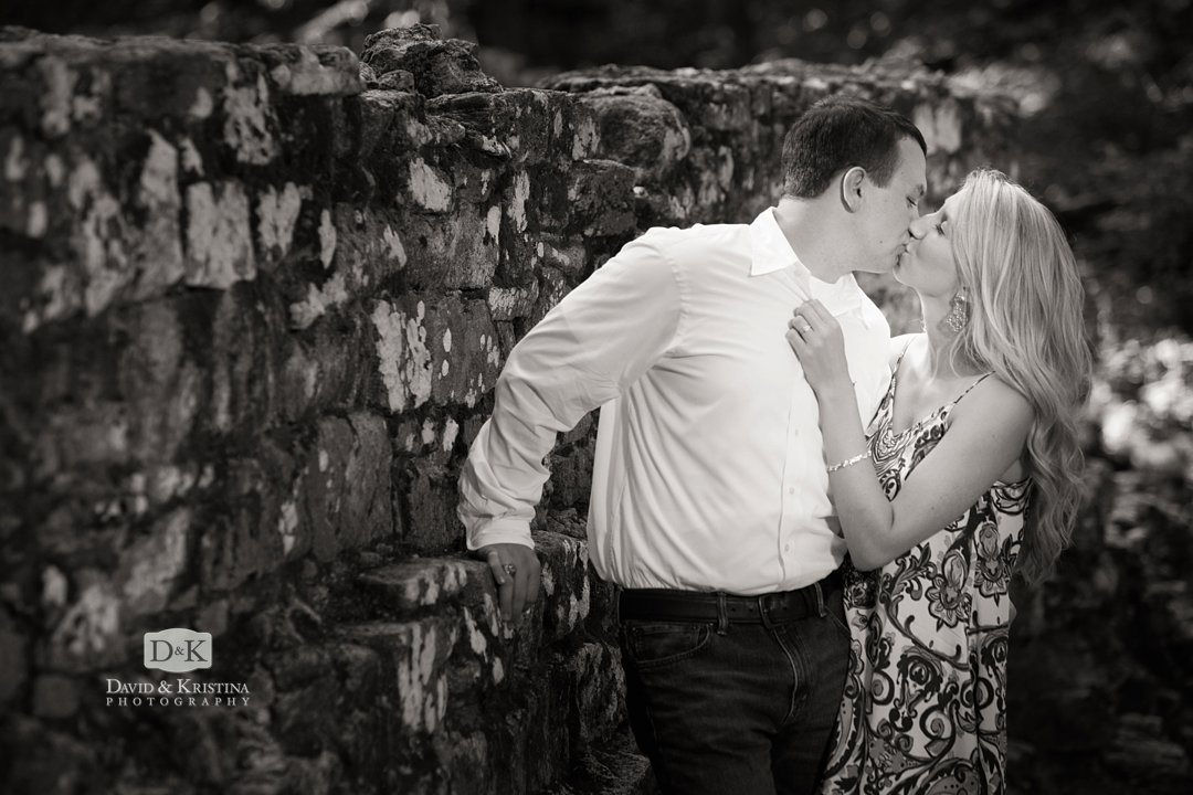kissing engagement picture at old stone bridge near North Greenville Poinsett Bridge