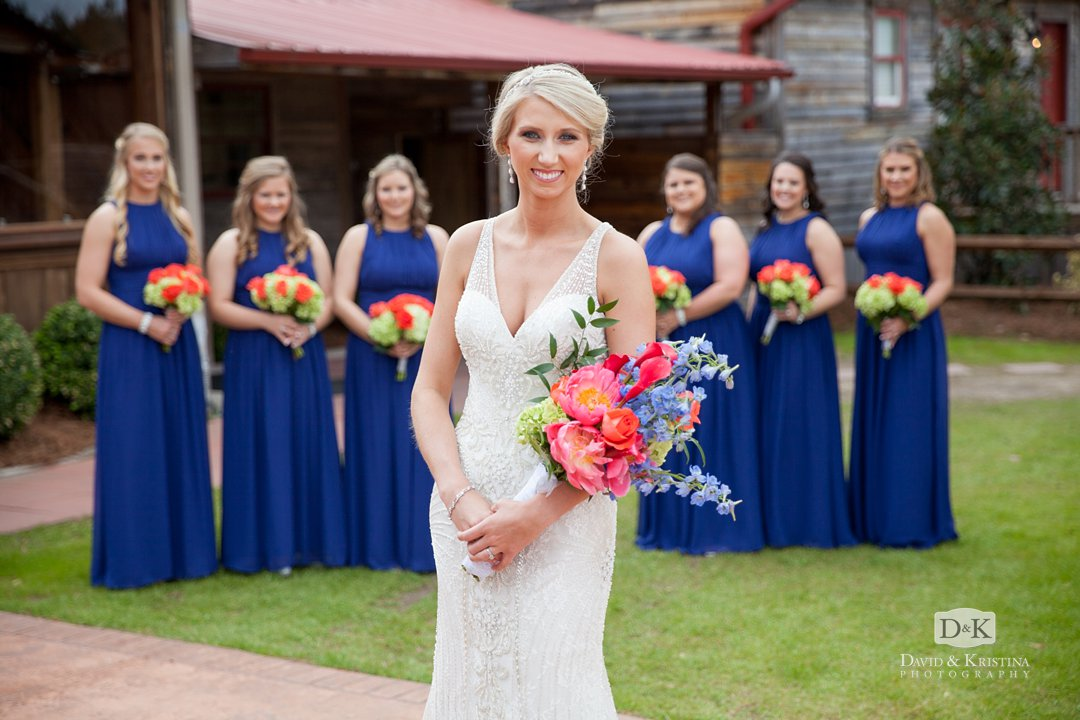 bride in front of bridesmaids in marine blue dresses