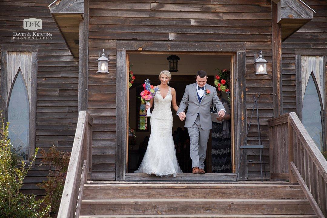 walking out front door of wedding chapel at Hidden Acres