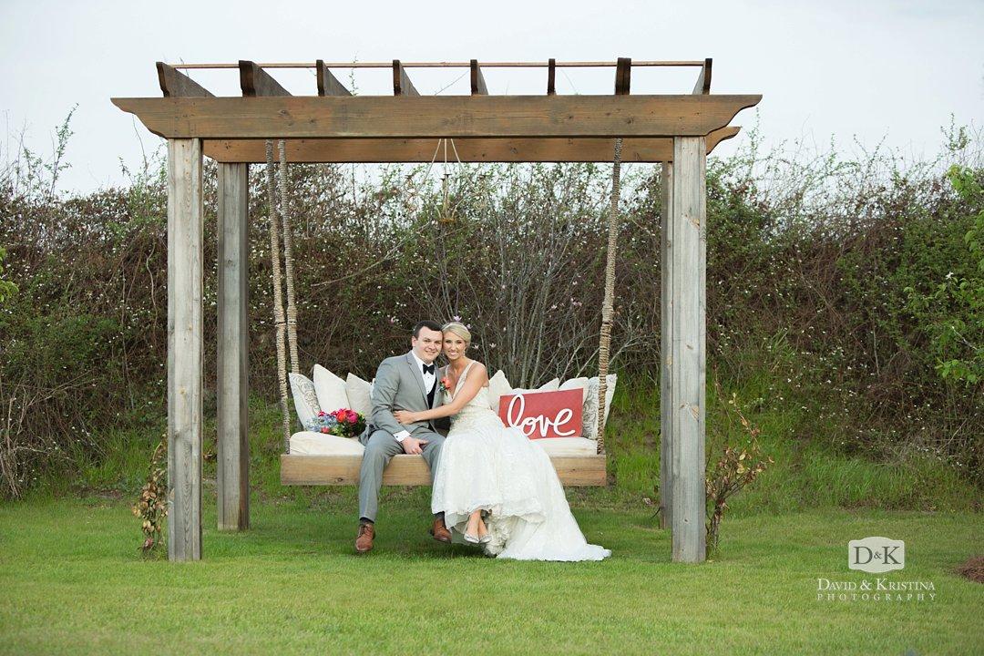 bride and groom in bench swing at Hidden Acres wedding