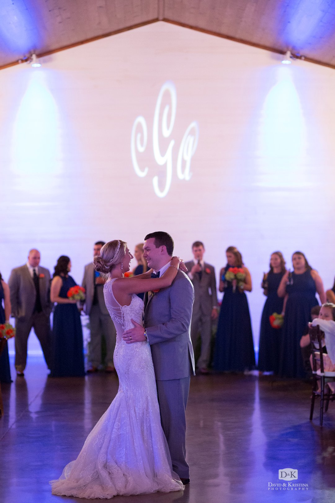 monogram light projected on wall during wedding reception
