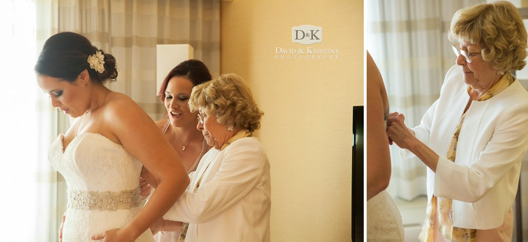 mother helping bride into dress