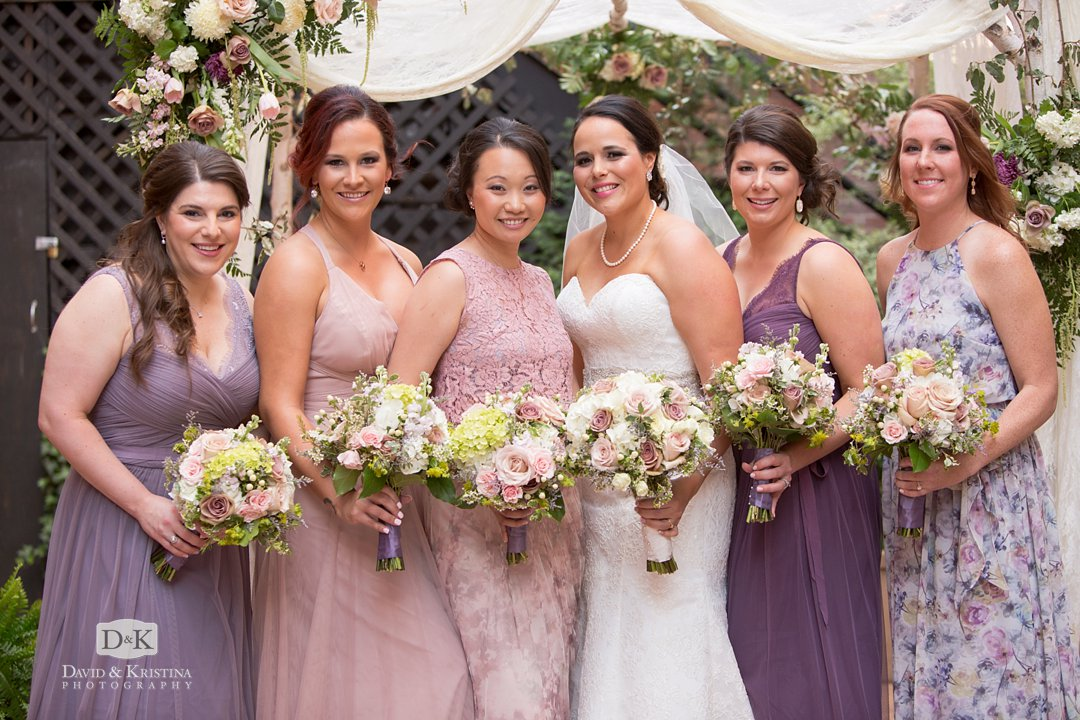bridesmaids in different dresses in a variety of purple and lavender