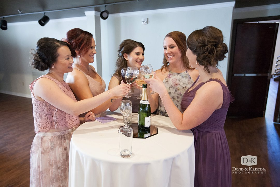 bridesmaids toasting with glasses of wine before the wedding ceremony