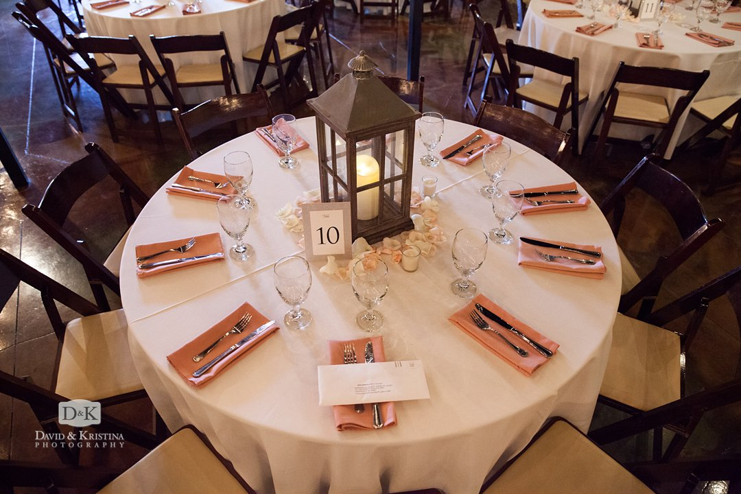 Round table with pink napkins and rustic lanterns