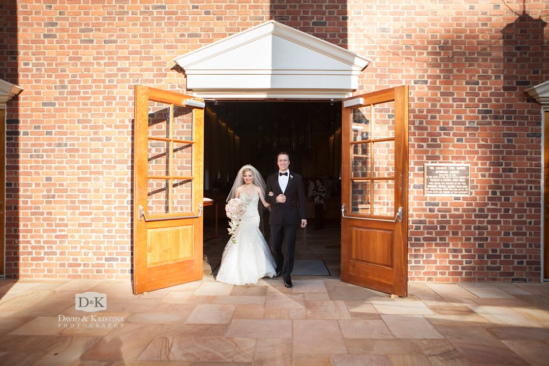 bride and groom walk out front door of Daniel Chapel at Furman