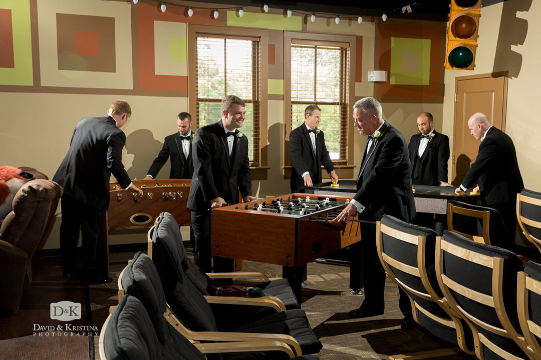 groomsmen playing foosball before wedding
