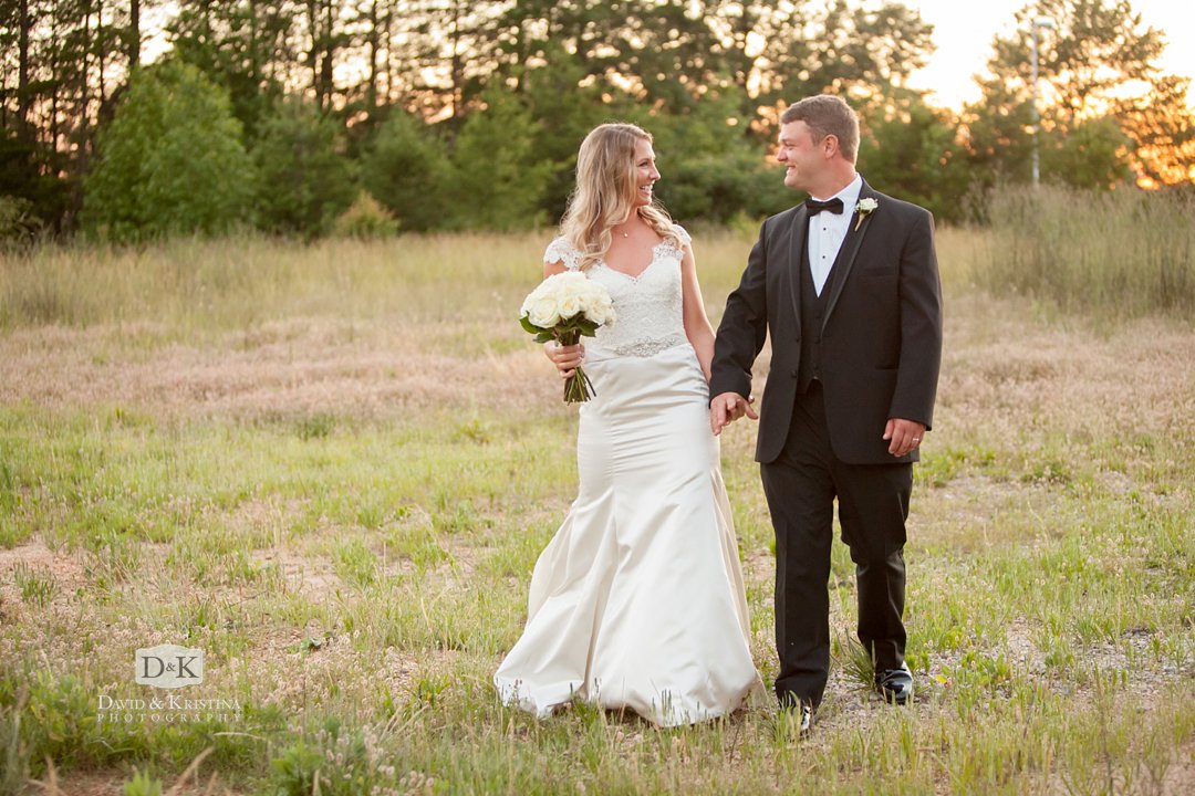 Bride and groom walking in grassy field at sunset