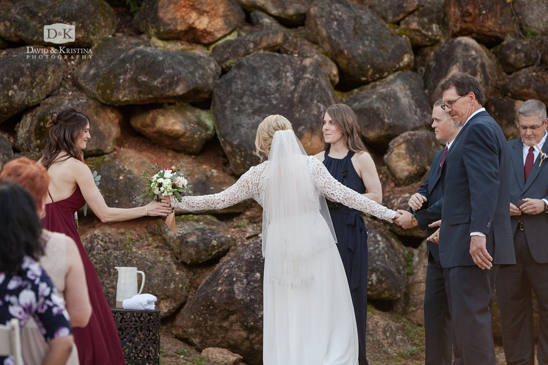 bride handing off bouquet to maid of honor