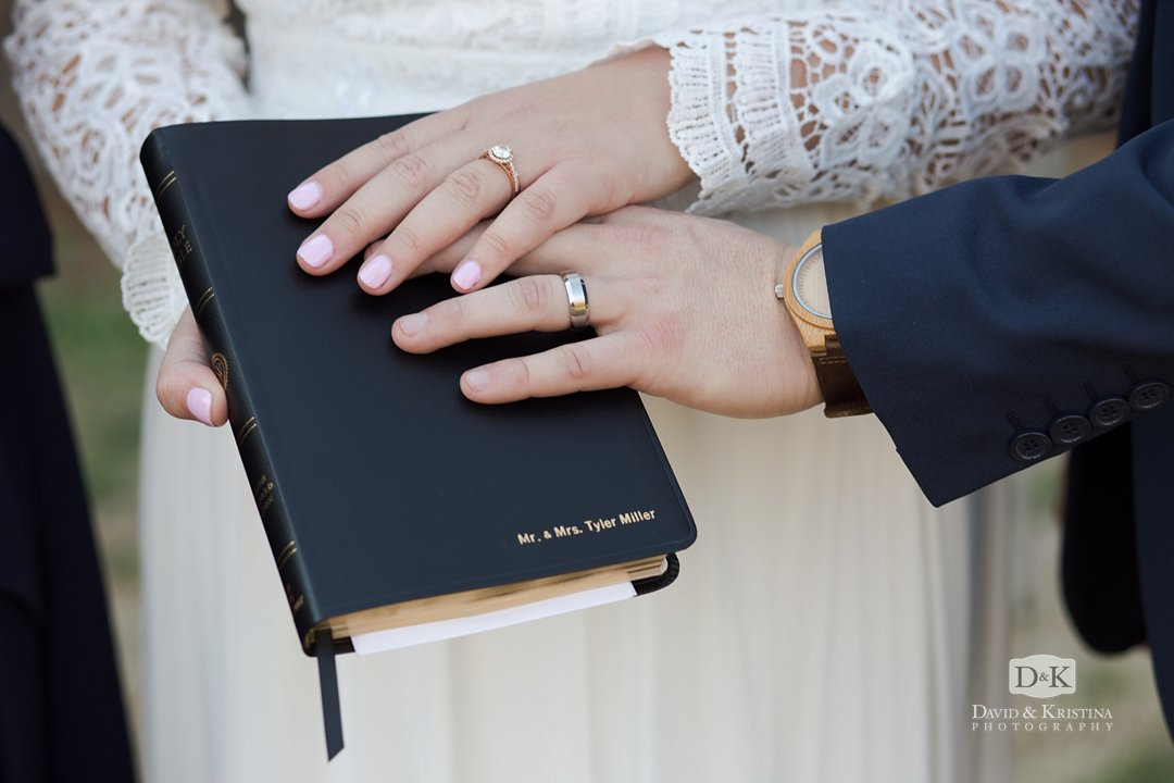 bride and groom's hands with rings on personalized Bible