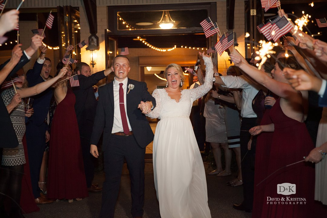 Bride and groom exit through waving american flags