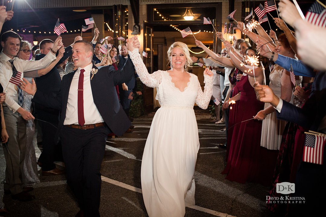 Bride and groom exit through waving american flags and sparklers