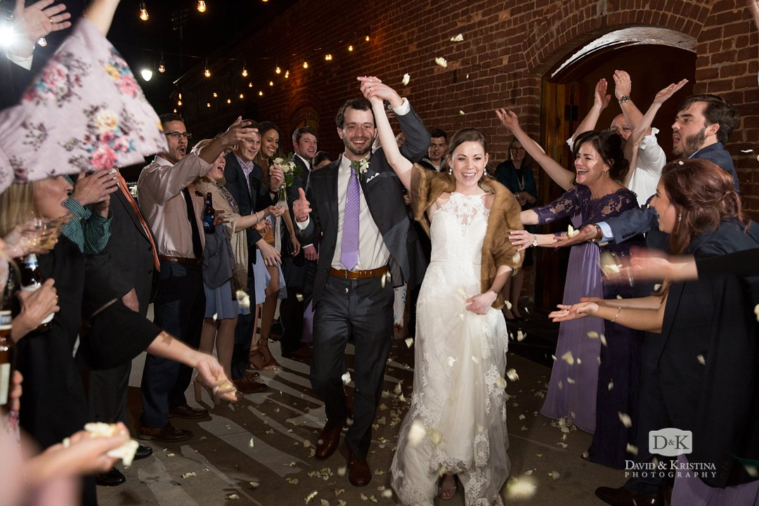 Bride and groom exit through flower petals on the deck of Old Cigar Warehouse