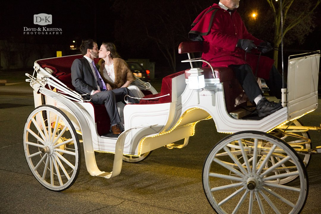 bride and groom depart in a horse drawn carriage by Whispering Winds Carriage Co.