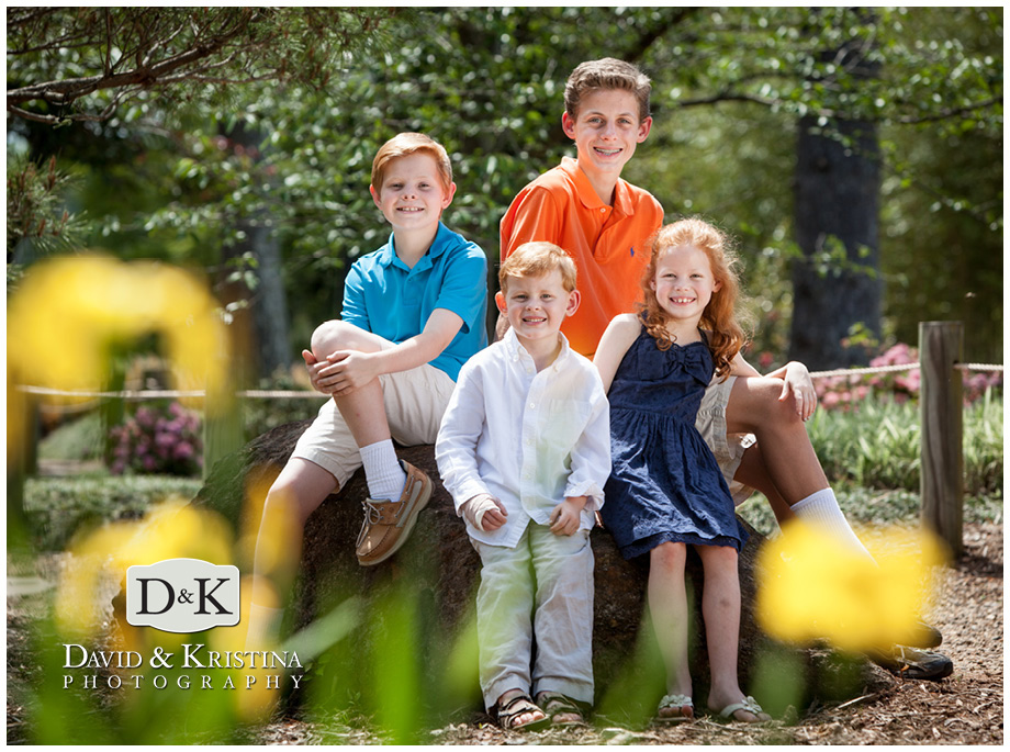 photo of just the kids sitting on a rock with flowers in the foreground