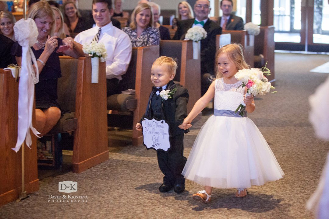 flower girl and ring bearer with sign here comes your Gal walking down the aisle